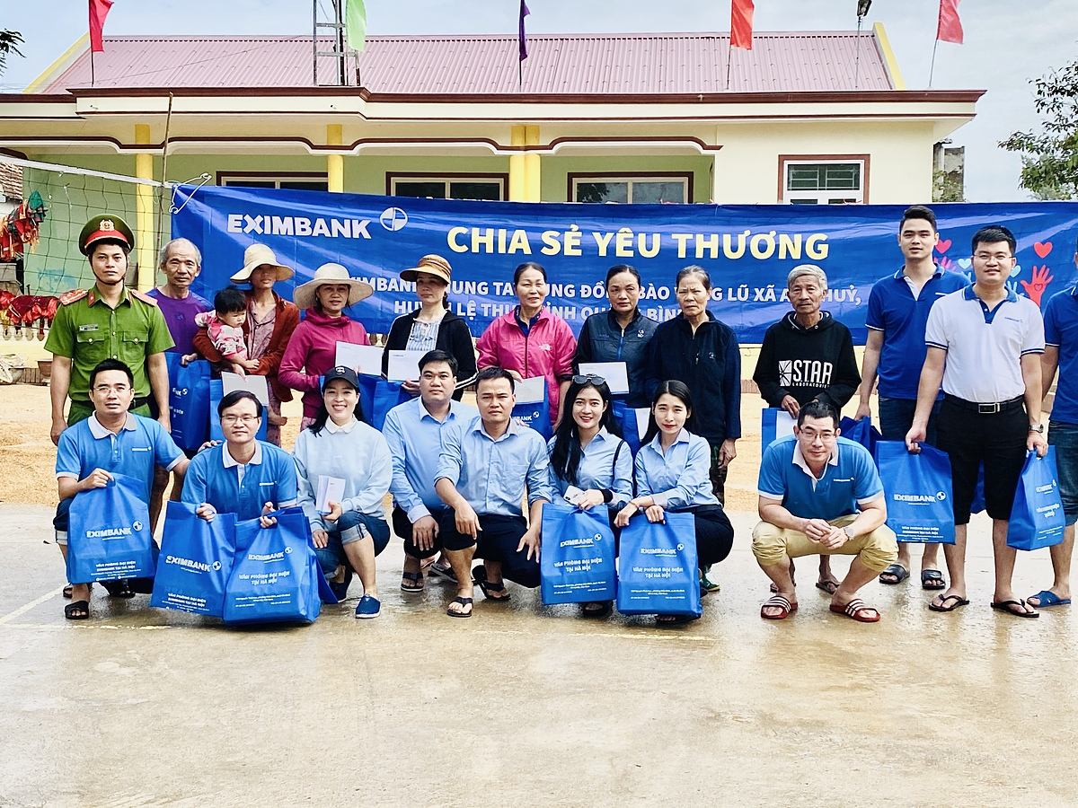 Tình nguyện viên Eximbank chup hình cùng bà con vùng rốn lũ Quảng Bình. Ảnh: Eximbank.