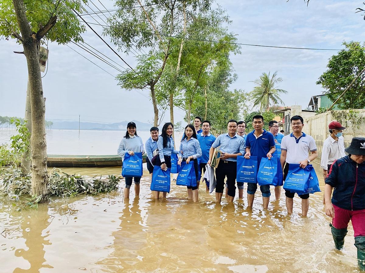 Đoàn thiện nguyện Eximbank lội nước vào tặng quà cho các hộ dân xã An Thủy, huyện Lệ Thủy, tỉnh Quảng Bình. Ảnh: Eximbank.