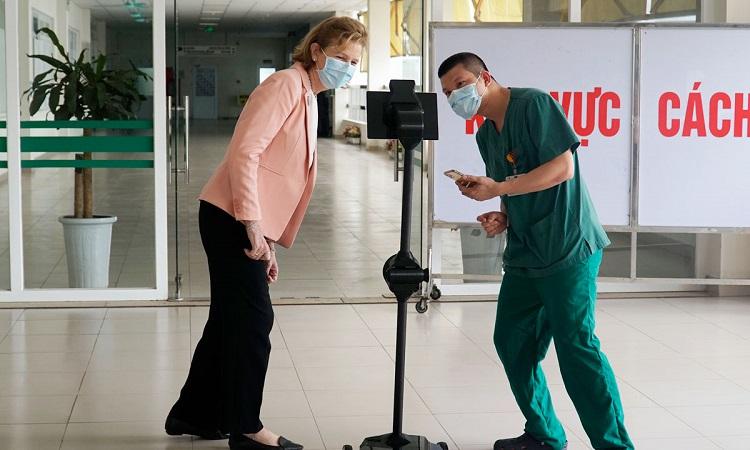 Bác sĩ Trần Văn Bắc, Phó trưởng khoa Cấp cứu Bệnh viện Nhiệt đới Trung ương (áo xanh) cùng bà Caitlin Wiesen, đại diện thường trú của UNDP tại Việt Nam, sử dụng robot Ohmni. Ảnh: UNDP.