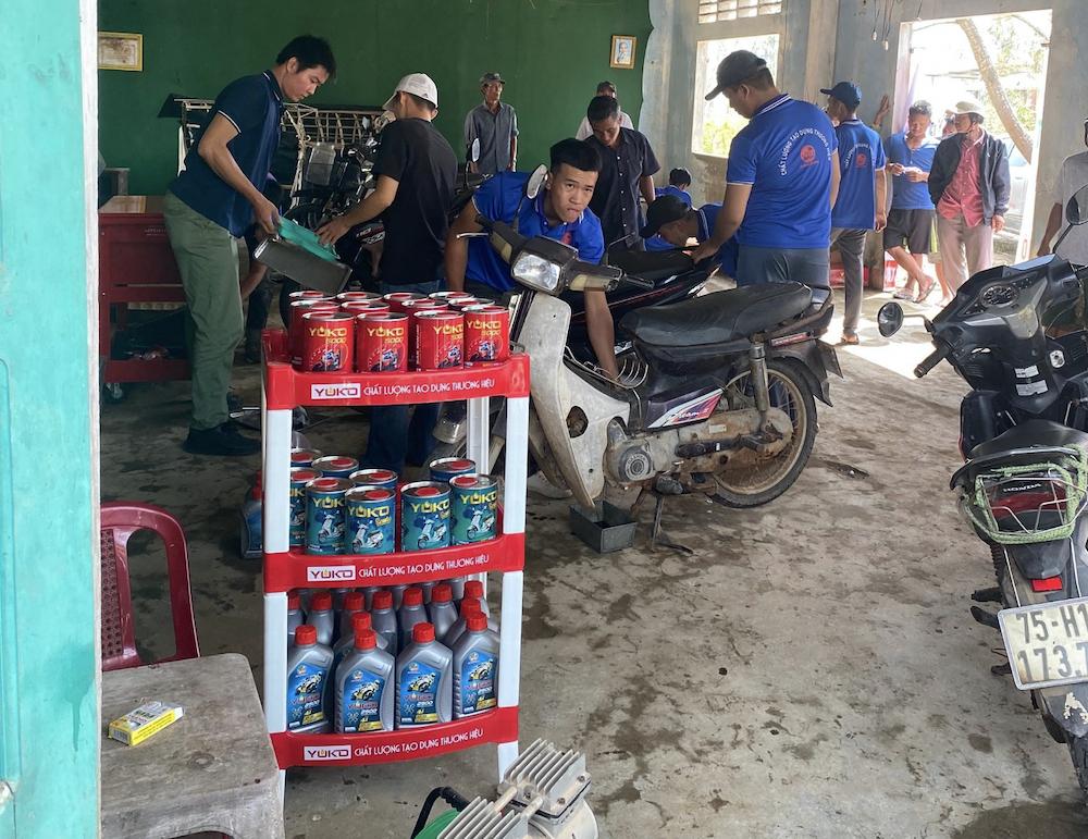 Các thợ thiện nguyện sửa xe và thay dầu... cho xe máy của người dân.