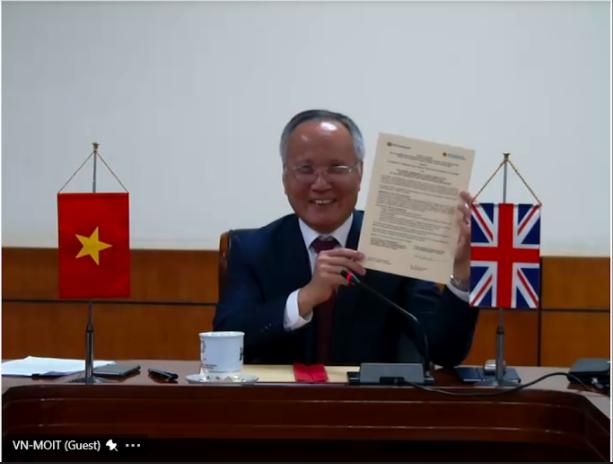 Thứ trưởng Công Thương Trần Quốc Khánh trao đổi ký kết hôm 12/11. Ảnh: Đại sứ quán Anh.