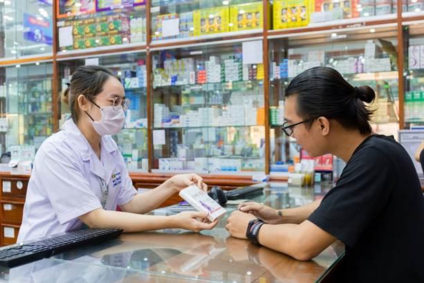 Một dược sĩ tư vấn cho khách mua thuốc.