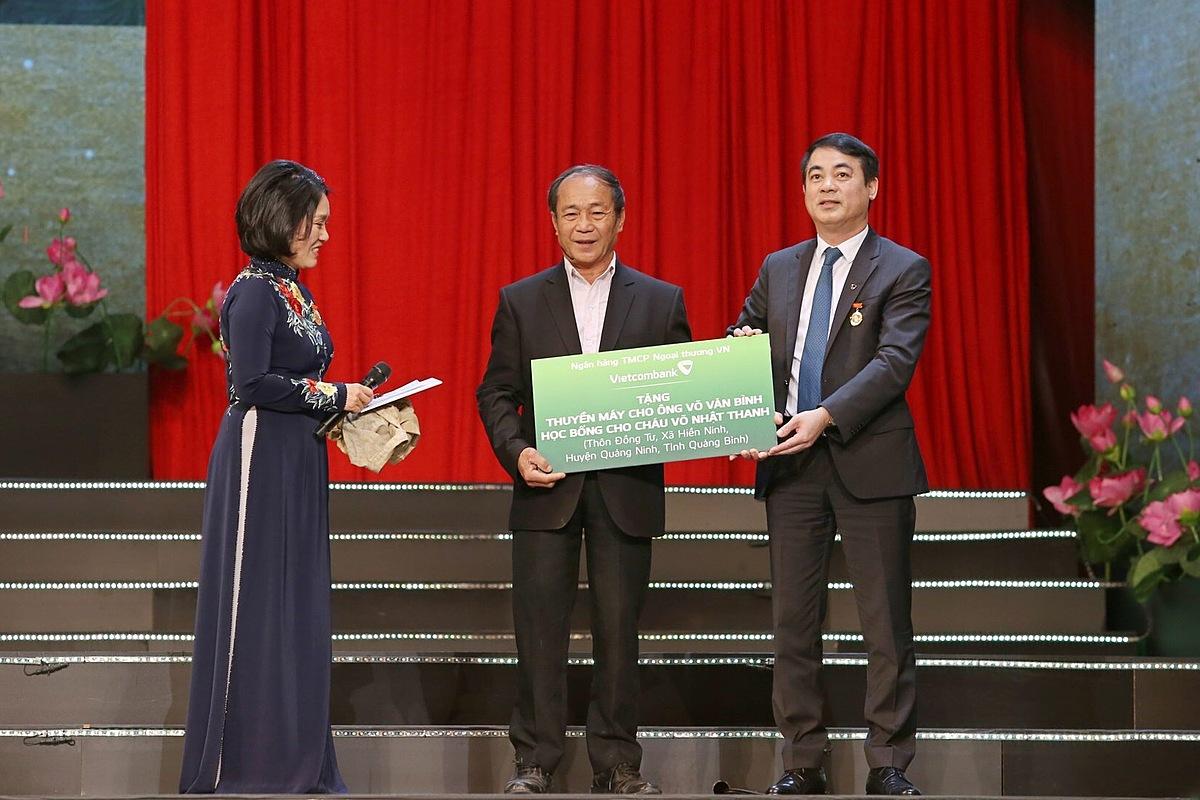 Ông Nghiêm Xuân Thành - Chủ tịch HĐQT Vietcombank, trao biển tượng trưng tặng thuyền máy cho ông Võ Văn Bình và học bổng cho cháu Võ Nhật Thanh.