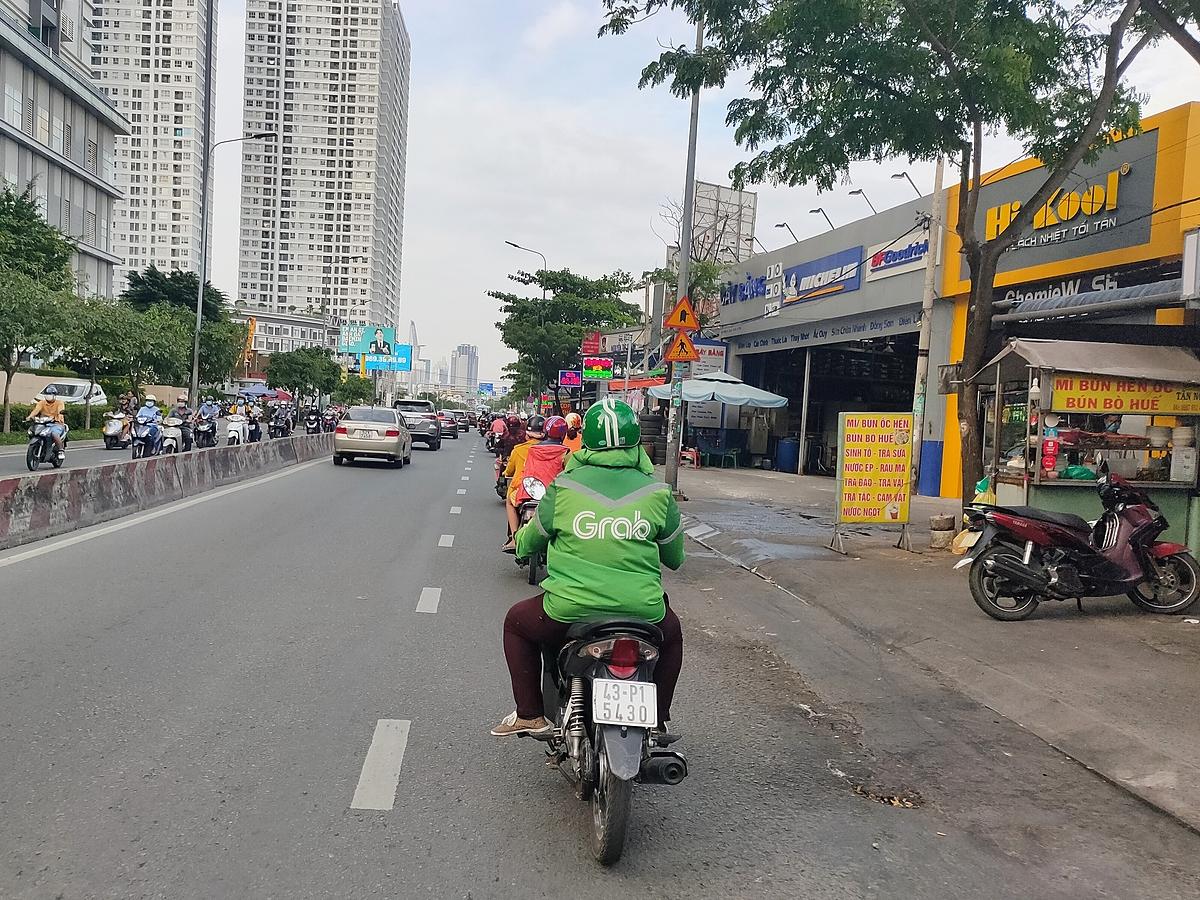 Một tài xế GrabBike đang di chuyển trên đường Nguyễn Hữu Thọ, quận 7, TP HCM ngày 29/12. Ảnh: Viễn Thông.