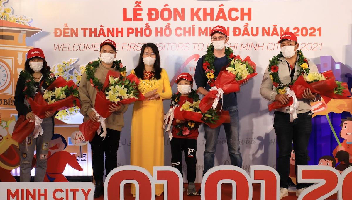 Giám đốc Sở Du lịch TP.HCM Nguyễn Thị Ánh Hoa (áo dài vàng) tặng hoa hành khách.