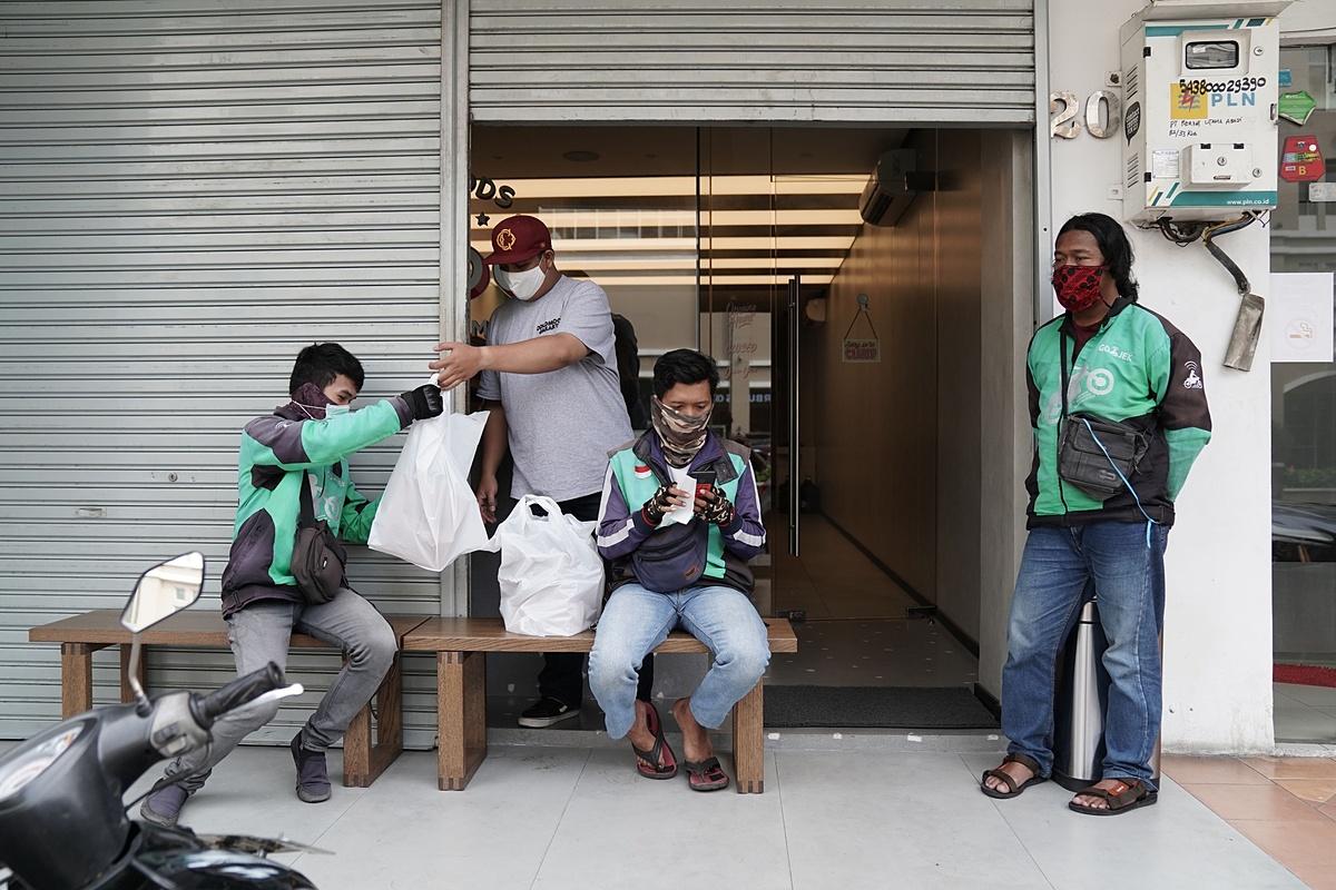Tài xế Gojek chờ nhận đồ bên ngoài một nhà hàng ở Jakarta. Ảnh: Bloomberg