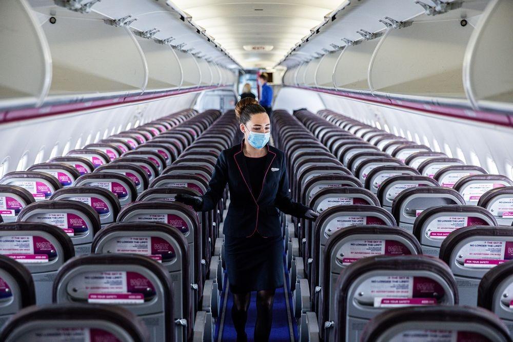 Một tiếp viên đeo khẩu trang đang kiểm tra cabin trước chuyến bay cất cánh từ Budapest. Ảnh: Bloomberg.