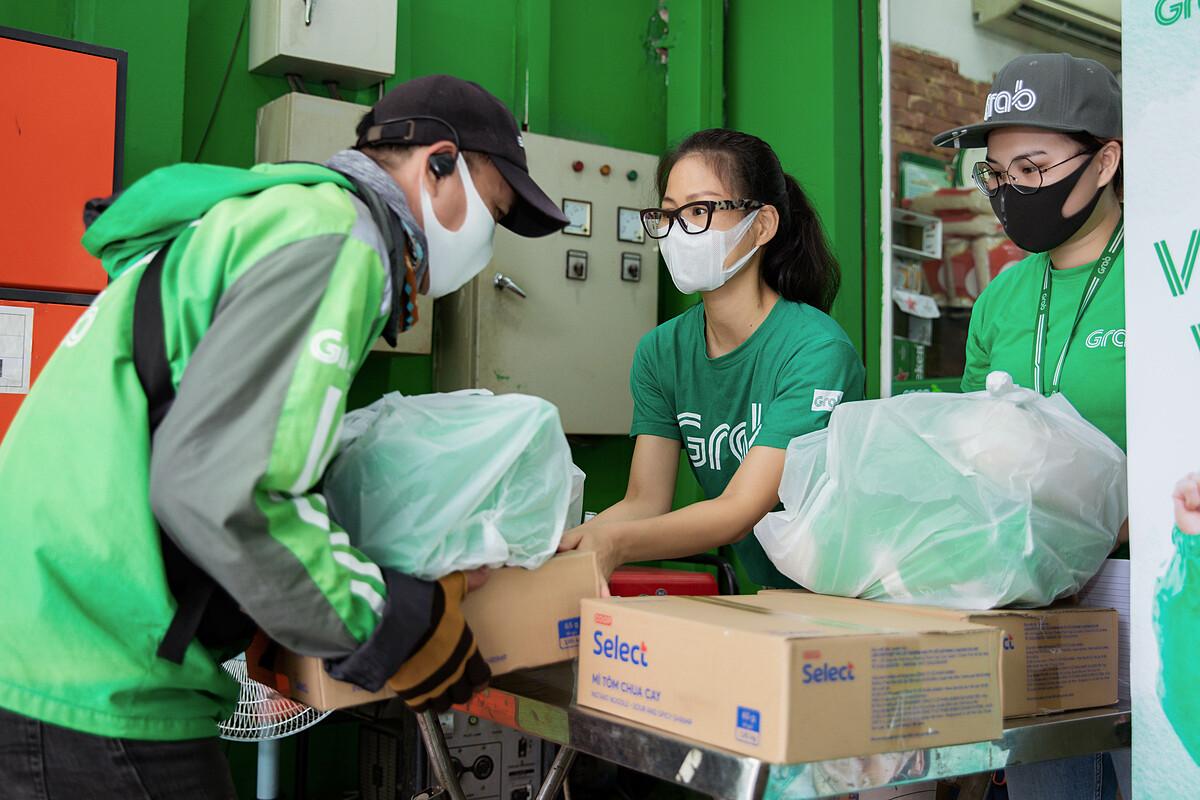 Bà Nguyễn Thái Hải Vân (giữa), Giám đốc điều hành Grab Việt Nam, trao quà hỗ trợ đối tác tài xế. Ảnh: Grab.