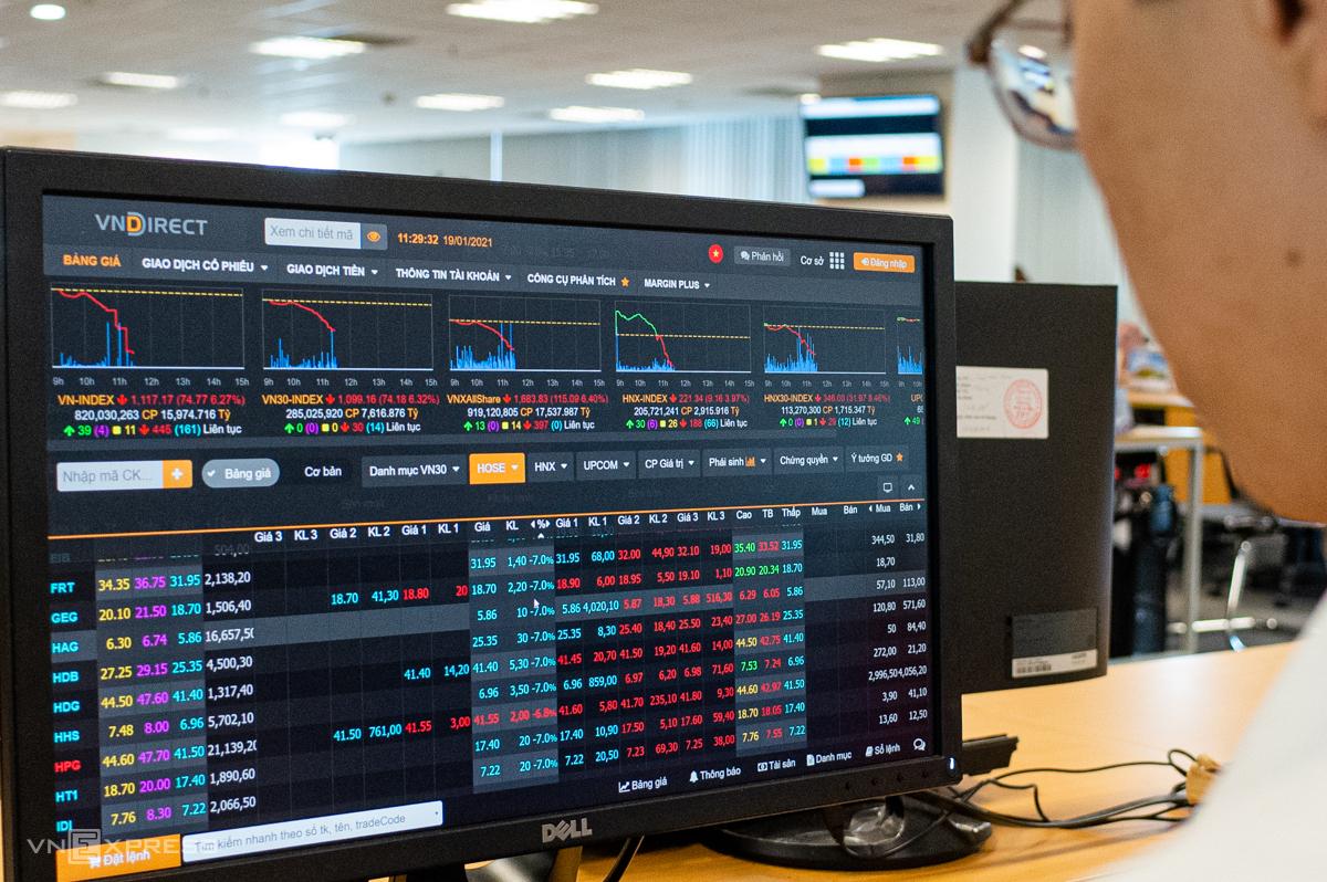 Nhà đầu tư theo dõi bảng giá khi VN-Index giảm sâu phiên sáng 19/1. Ảnh: Thành Nguyễn.