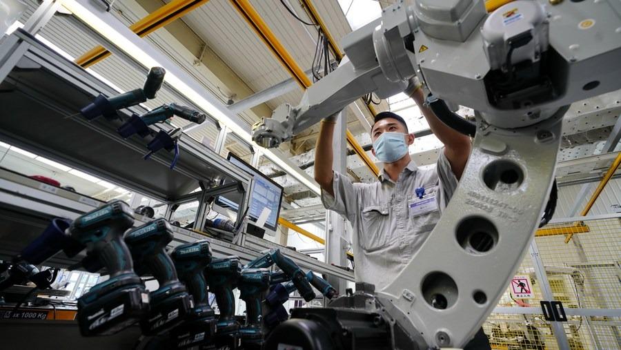 Một công nhân điều chỉnh robot hàn tại một công ty sản xuất thiết bị hàn ở Đường Sơn, tỉnh Hà Bắc, Trung Quốc, ngày 16/7/2020. Ảnh: Xinhua.