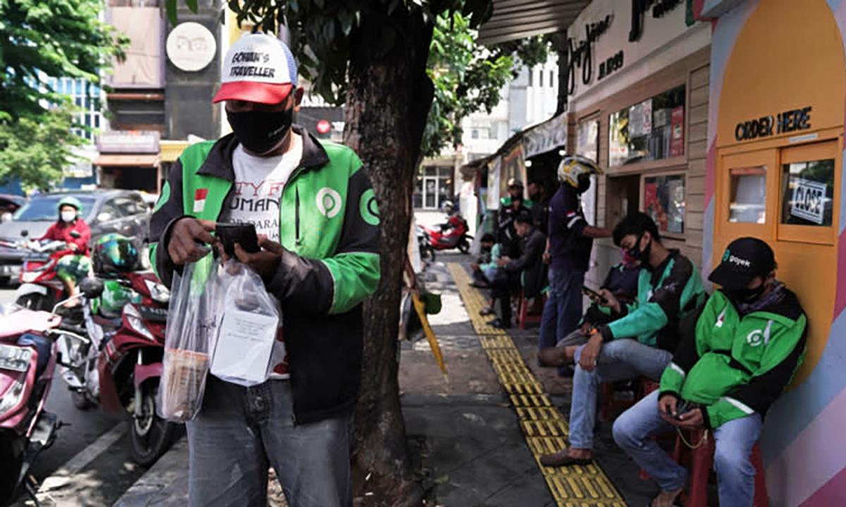 Các tài xế lấy đồ ăn trước một cửa hàng tại Jakarta, Indonesia. Ảnh: Nikkei