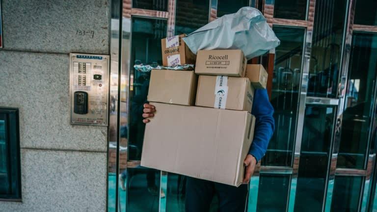 Một nhân viên của CJ Logistics bê đống hàng vượt mặt tại Gangnam, Seoul. Ảnh: Nikkei