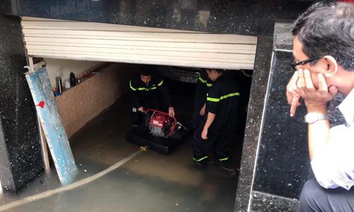 Máy bơm được đưa xuống hầm để bơm nước ra, cứu hộ ôtô đang bị ngập tại tòa nhà ở quận 5, TP HCM. Ảnh: Song Ngư
