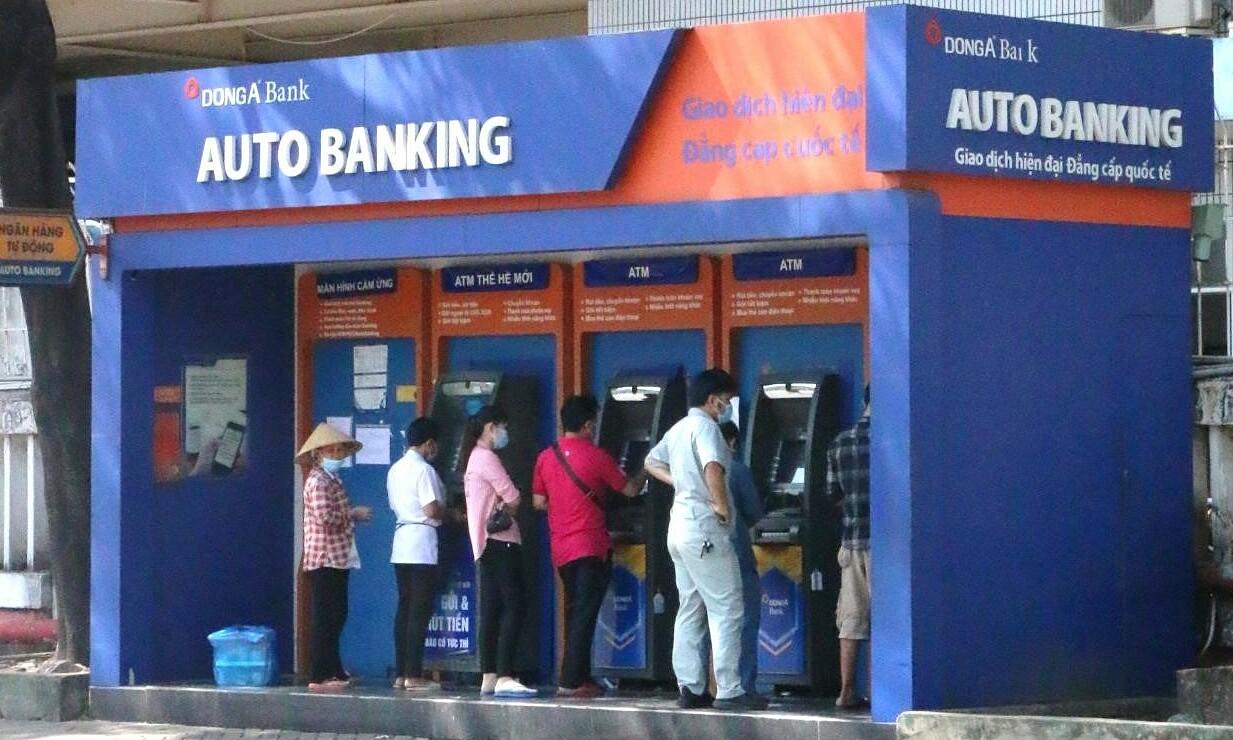 Khách hàng đang giao dịch tại các máy ATM vừa được DongA Bank lắp đặt mới trong tháng 1 tại công ty Pouyuen (quận Bình Tân, TP HCM). Ảnh: DongA Bank.