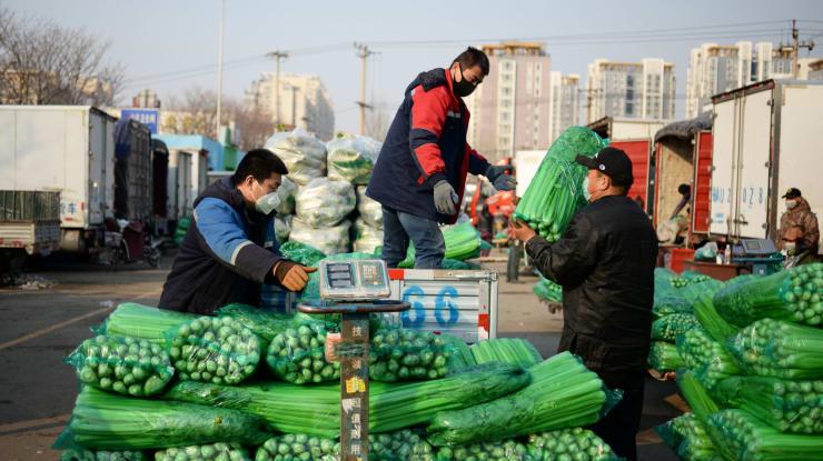 Người dân vận chuyển rau tại một chợ đầu mối ở Bắc Kinh (Trung Quốc). Ảnh:Reuters