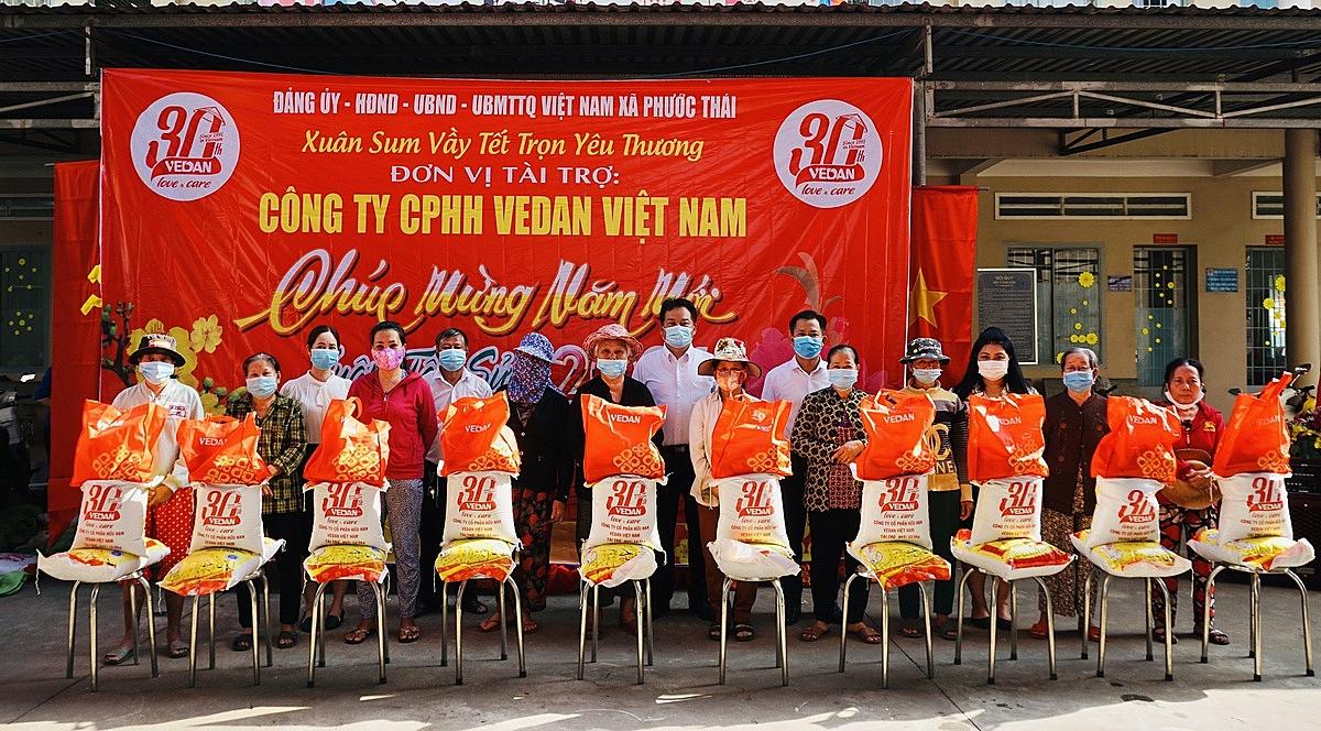 Đại diện công ty Vedan Việt Nam (áo trắng, đứng giữa) cùng đại diện ban ngành tỉnh Đồng Nai trao quà Tết cho bà con tại địa phương