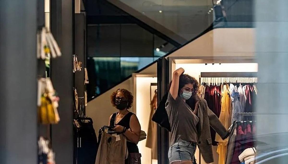 Một người mua sắm thử quần áo tại một cửa hàng ở New York ngày 5/7/2020. Ảnh: Reuters.