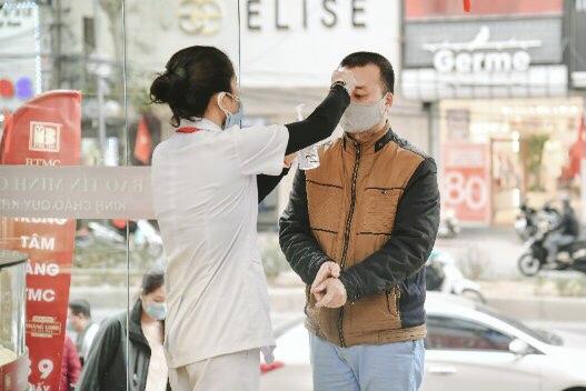 Khách hàng rửa tay, đo thân thiệt trước khi vào cửa hàng. Ảnh: Bảo Tín Minh Châu.