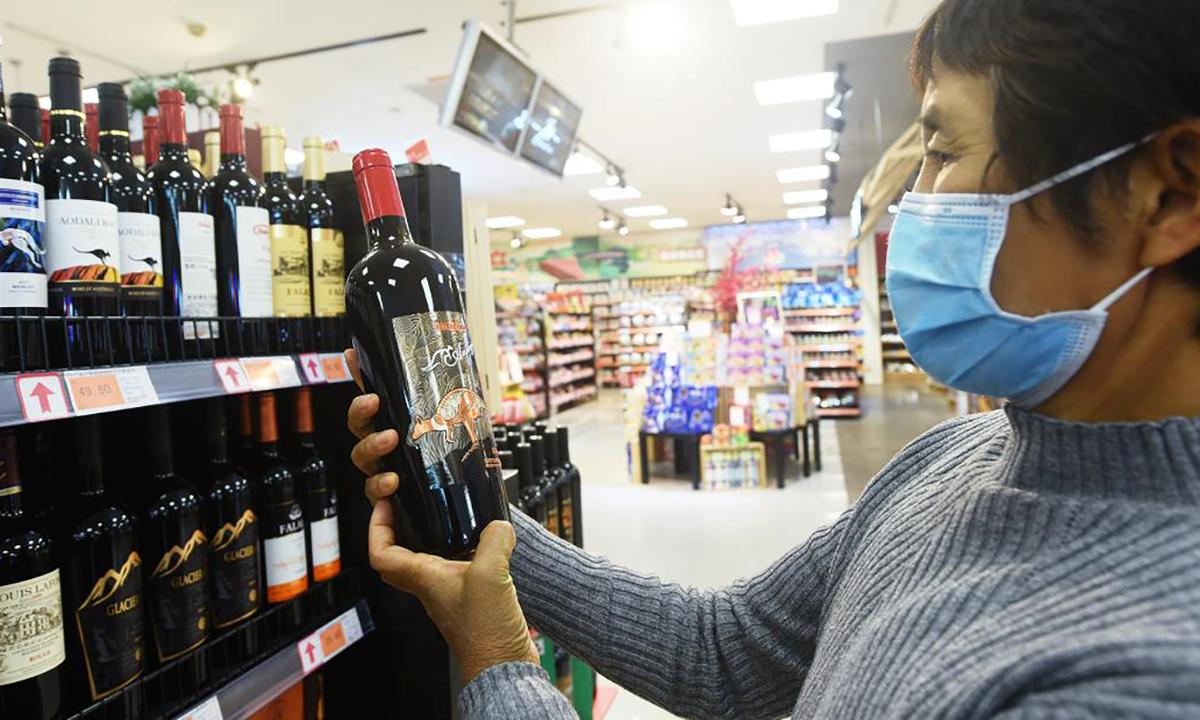 Khách hàng cầm trên tay chai rượu vang Australia tại một siêu thị ở Hàng Châu hồi tháng 11/2020. Ảnh: CNN