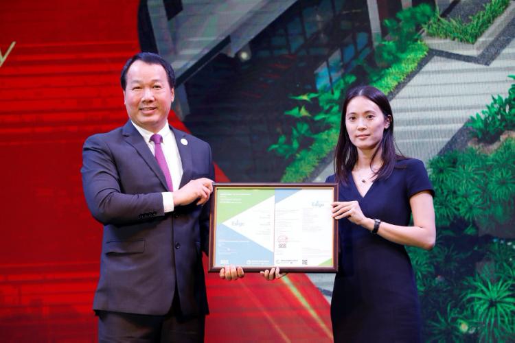 Ông Bùi Duy Toàn - Giám đốc Khối kinh doanh tiếp thị Công ty TNHH Phú Mỹ Hưng (trái) nhận chứng chỉ công trình thiết kế theo tiêu chuẩn EDGE từ đại diện Tổ chức Tài chính Quốc tế IFC. Ảnh: Hữu Khoa.