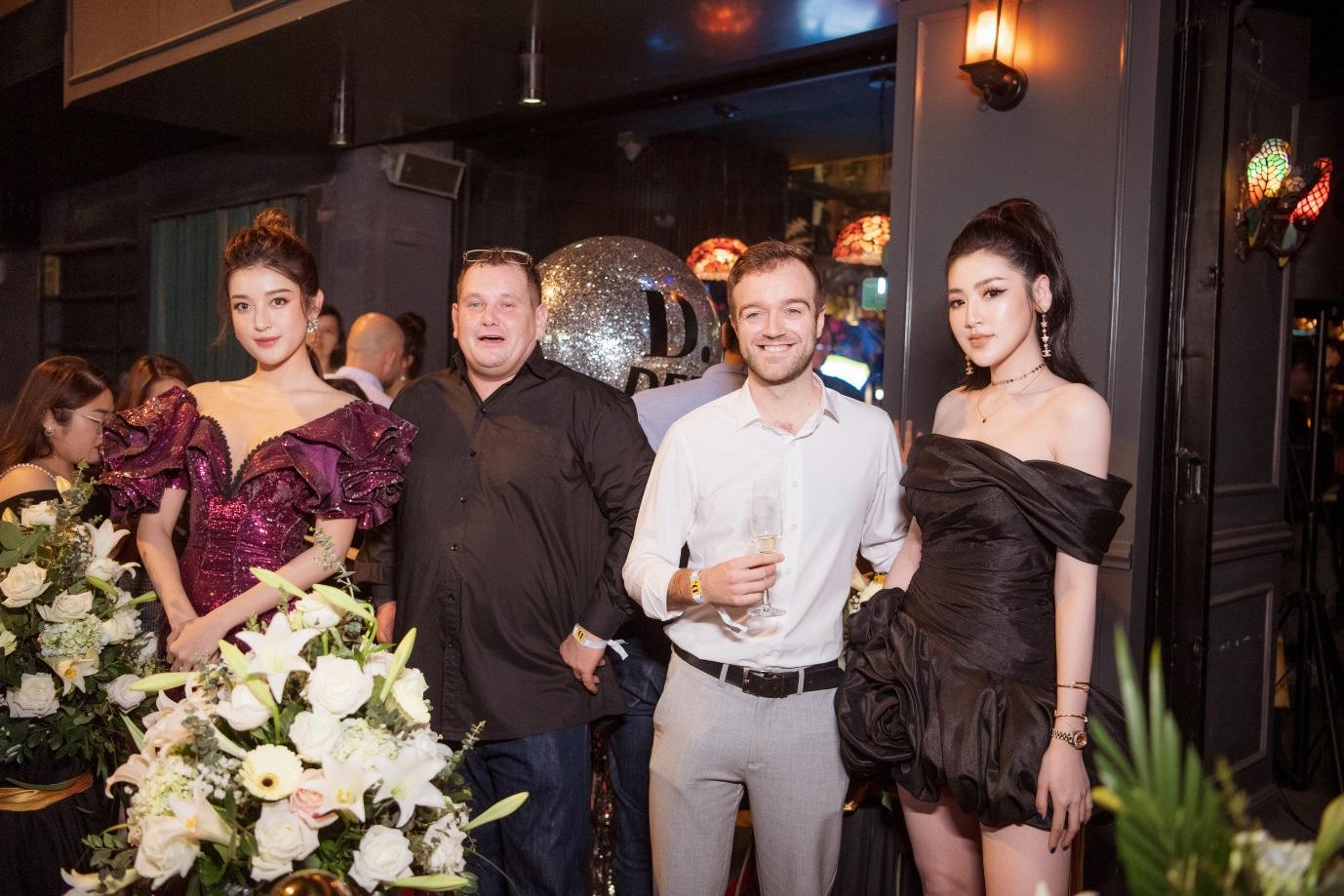 Huyền My (ngoài tùng bên trái) và Tú Anh (ngoài cùng bên phải) chụp ảnh cùng CEO Adam Christopher Chaplin (áo đen) và khách mời tại buổi tiệc.