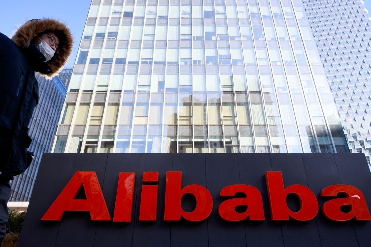 Một người đeo khẩu trang đi qua trụ sở của Alibaba tại Trung Quốc. Ảnh: Reuters.