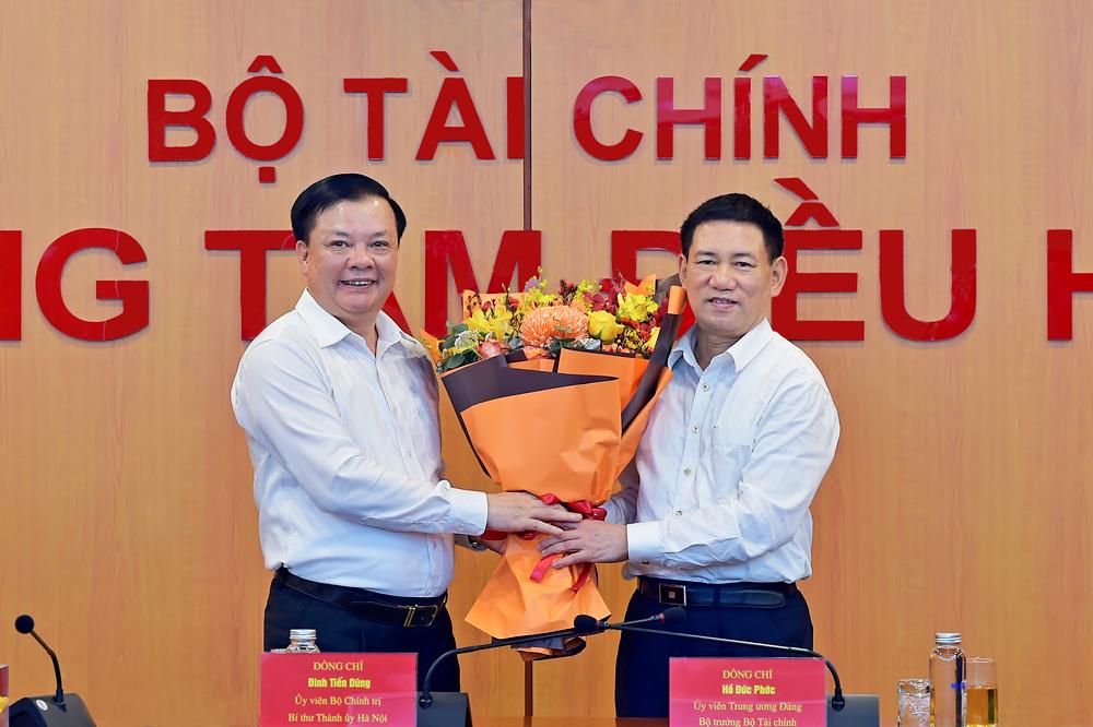 Nguyên Bộ trưởng Tài chính Đinh Tiến Dũng (bên trái) tặng hoa cho Tân Bộ trưởng Hồ Đức Phớc. Ảnh: Bộ Tài chính.