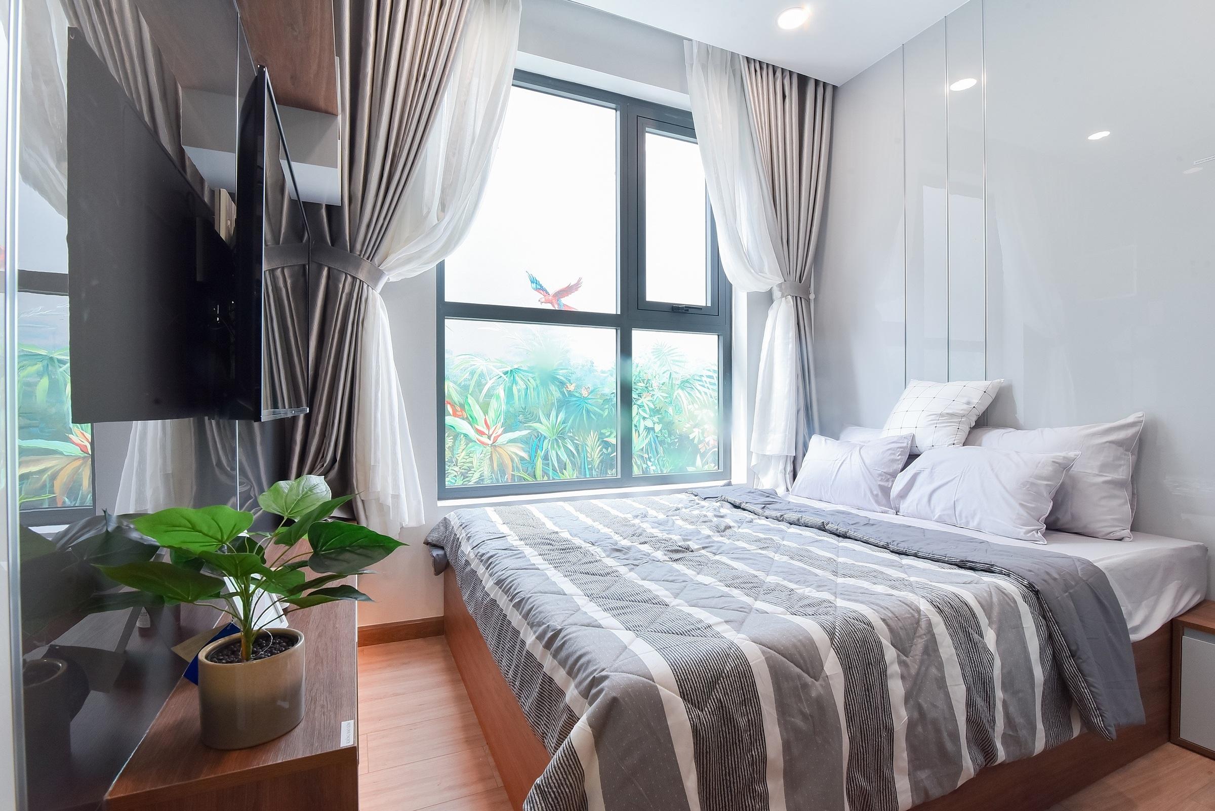 Bcons gợi ý cách thiết kế để tăng độ rộng cho phòng ngủ với sàn ốp gỗ, đón ánh sáng và khí trời qua hệ thống cửa sổ lớn.