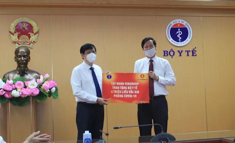 Bộ trưởng Y tế Nguyễn Thanh Long (trái) tiếp nhận hỗ trợ khoản tiền tương đương 4 triệu liều vaccine từ Tập đoàn Vingroup. Ảnh: Bộ Y tế