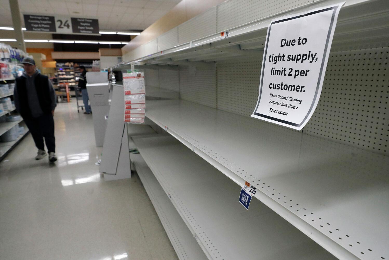 Do thiếu nguồn cung, một siêu thị yêu cầu khách chỉ lấy tối đa 2 sản phẩm mỗi người nhưng cũng không còn mặt hàng nào trên kệ. Ảnh: AP.