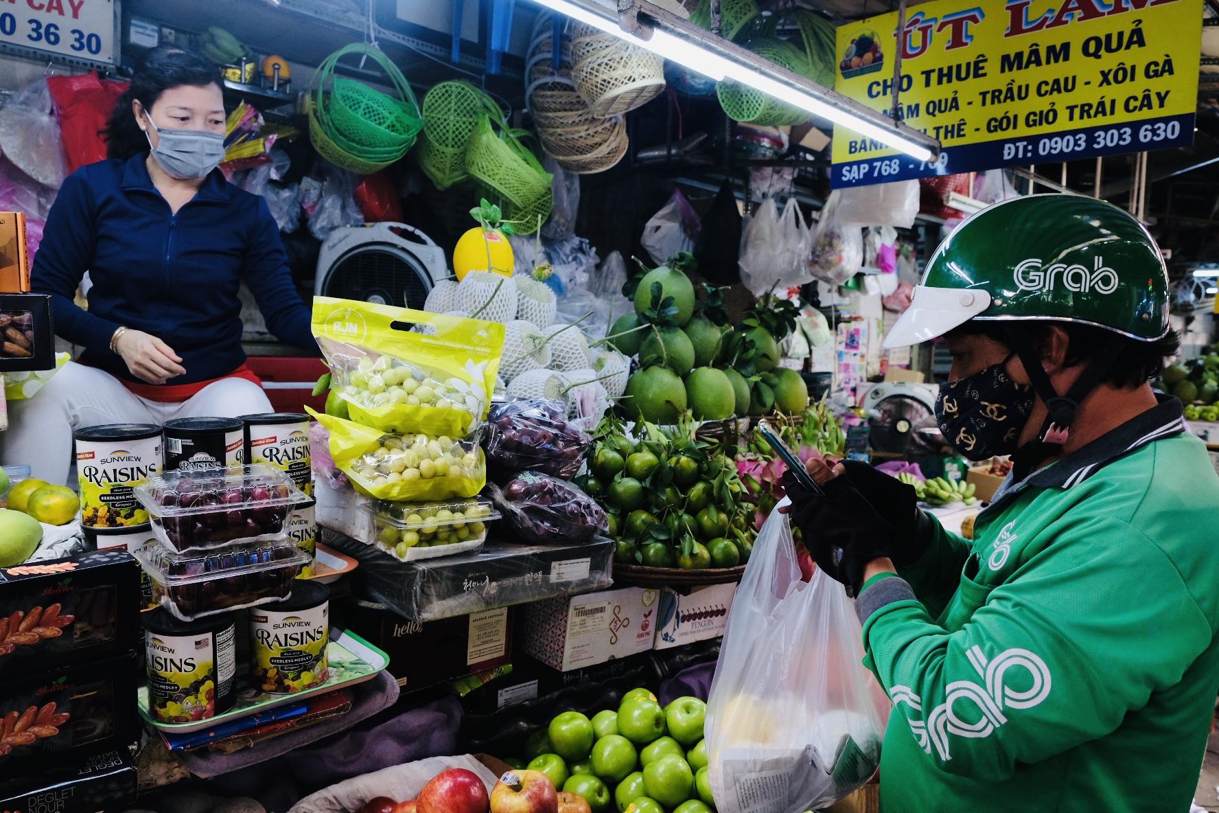 Một đối tác tài xế Grab đang nhận đơn hàng trái cây từ một tiểu thương chợ truyền thống.