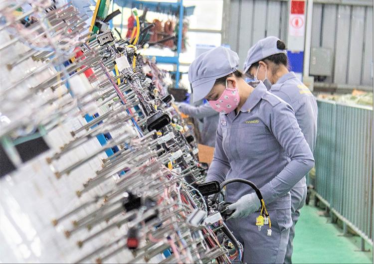 Công nhân tại dây chuyền lắp ráp dây điện ôtô trong nhà máy của Thaco Auto.
