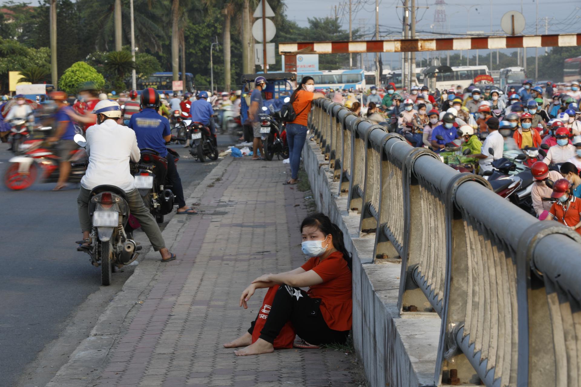 Một công nhân Pouyeun nghỉ mệt trên đườg về sau giờ tan ca ngày 3/6/2021, thời điểm công ty này chưa dừng hoạt động để chống dịch. Ảnh: Quỳnh Trần.