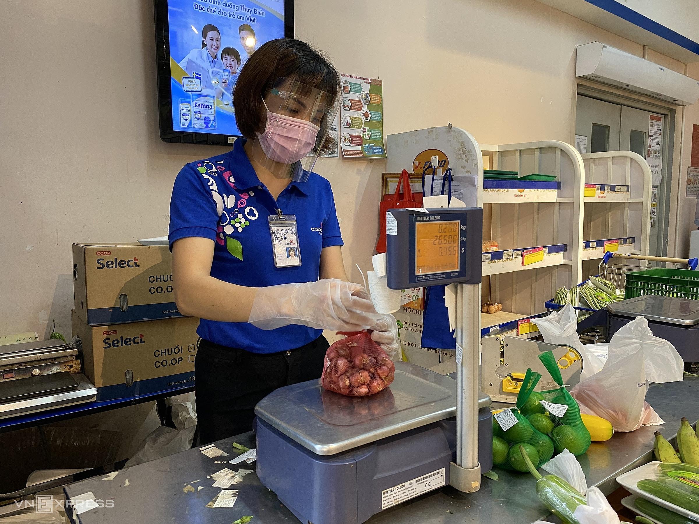 Nhân viên cân hàng tại siêu thị Co.op Mart Đồng Văn Cống làm việc hầu như không nghỉ tay. Ảnh: Tất Đạt.