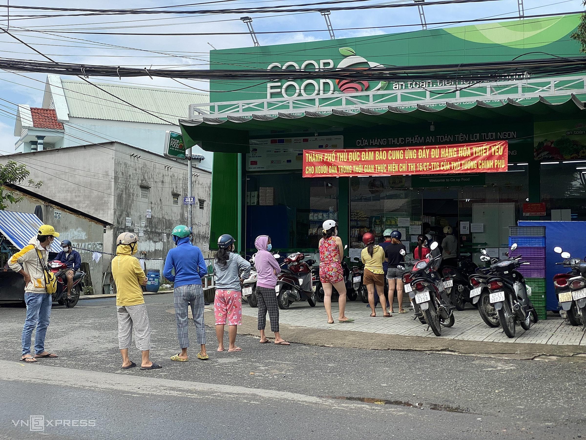 Người dân xếp hàng dài ra đến mặt lộ để chờ đến lượt mua sắm tại cửa hàng Co.op Food trên đường Lã Xuân Oai (Long Trường, TP Thủ Đức). Ảnh: Tất Đạt.