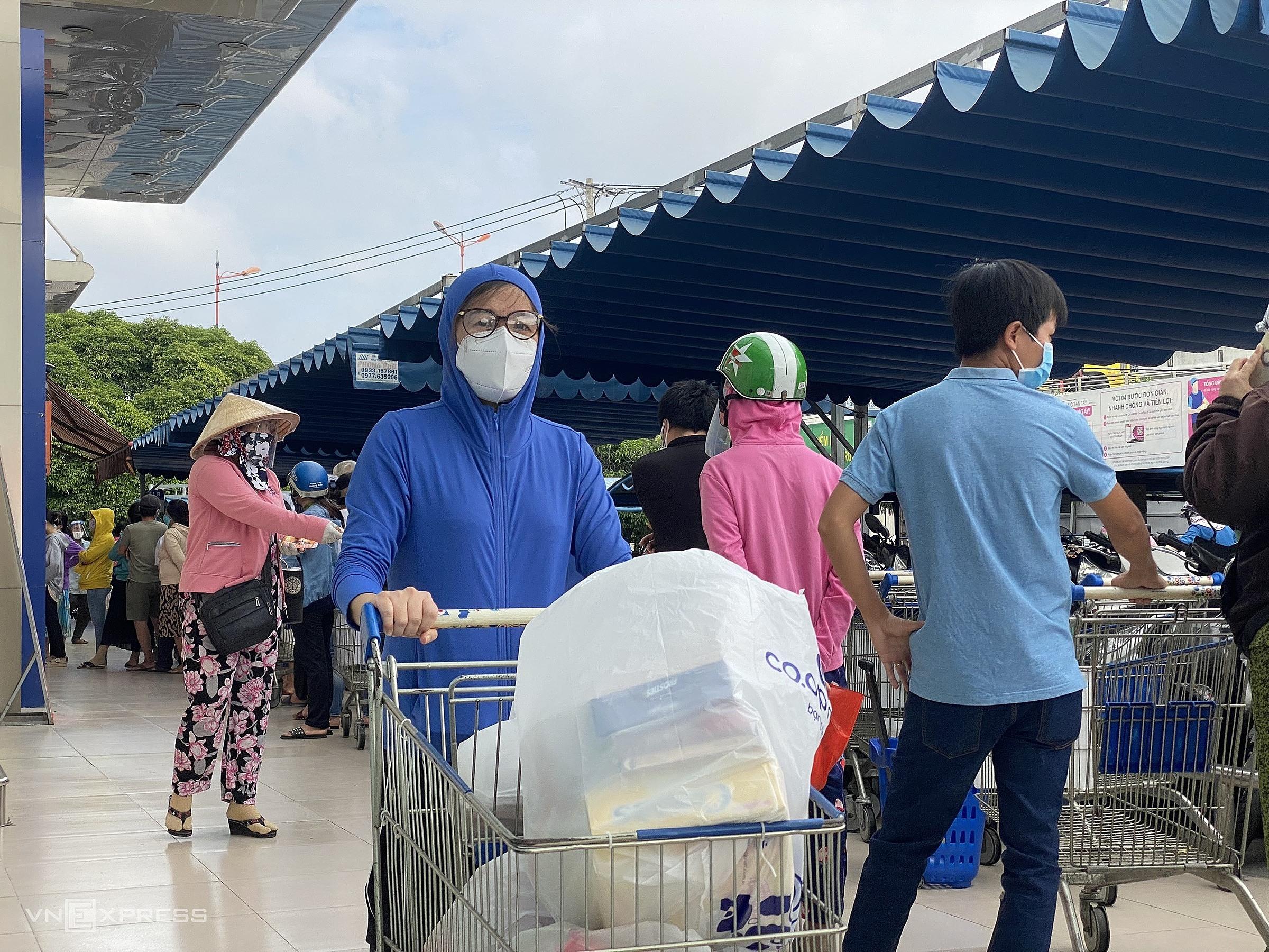 Một người dân đẩy xe hàng đầy ắp ra khỏi siêu thị Co.op Mart Xa lộ Hà Nội (Hiệp Phú, TP Thủ Đức) hôm 7/7. Ảnh: Tất Đạt.