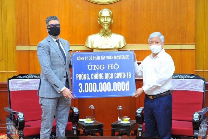 Đại diện Masterise Group (trái) trao biểu trưng số tiền ủng hộ cho ông Đỗ Văn Chiến - Chủ tịch Ủy ban Trung ương Mặt trận Tổ quốc Việt Nam, hôm 21/5. Ảnh: Masterise Group.