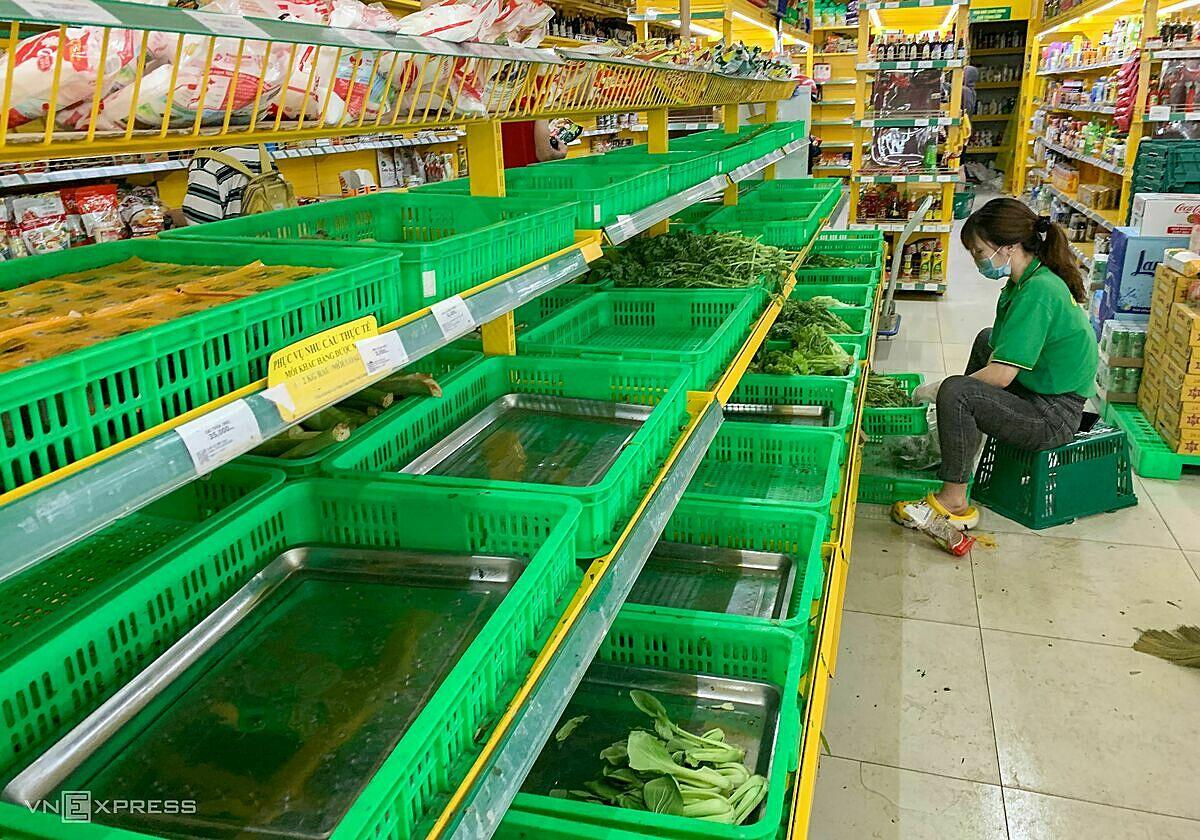 Nhân viên siêu thị Bách hoa xanh ở TP Thủ Đức bên quầy rau trống ngày 14/7. Ảnh:Quỳnh Trần.