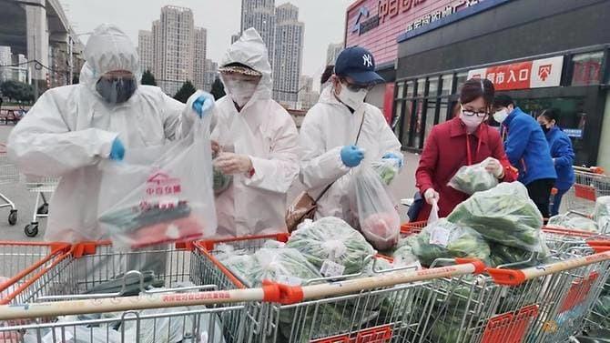 Nhân viên siêu thị và tình nguyện viên lên phân đơn hàng trực tuyến cho người dân ở Vũ Hán, Trung Quốc khi thành phố này bị phong tỏa năm 2020. Ảnh: Reuters.