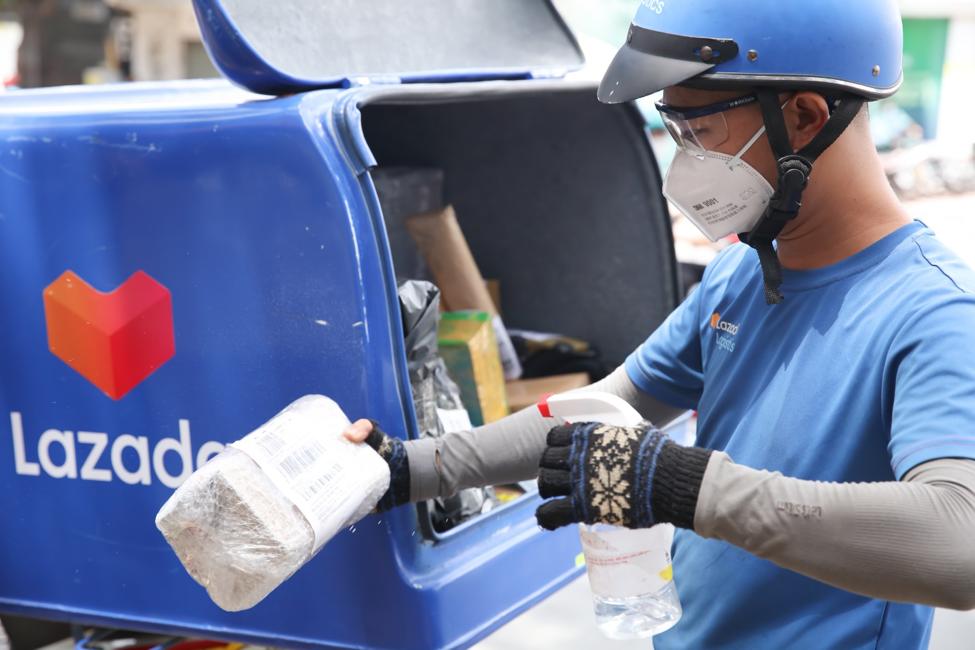 Nhân viên giao hàng Lazada tiến hành khử khuẩn gói hàng, trang bị đầy đủ đồ bảo hộ phòng dịch, áp dụng giao hàng không tiếp xúc nhằm đảm bảo an toàn cho cả khách hàng lẫn bản thân. Ảnh: Lazada Việt Nam.