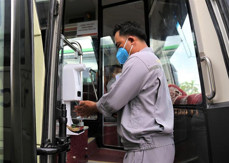 Một tài xế sát khuẩn tay trước khi lên phục vụ người dân.