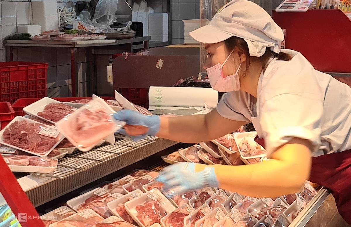 Nhân viên một siêu thị sắp xếp, đưa hàng thịt tươi sống vào quầy kệ. Ảnh: Minh Minh