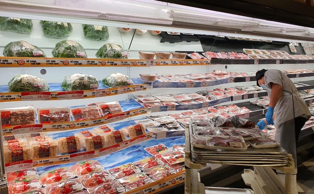 Nhân viên siêu thị Aeon tại Hà Nội tiếp thêm hàng thịt tươi sống lên quầy kệ. Ảnh: Phương Ánh