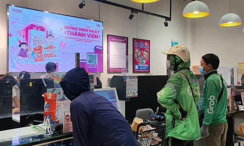 Tài xế Grab chờ nhận hàng tại siêu thị Aeon Mall Hà Đông sáng 24/7. Ảnh: Đức Minh