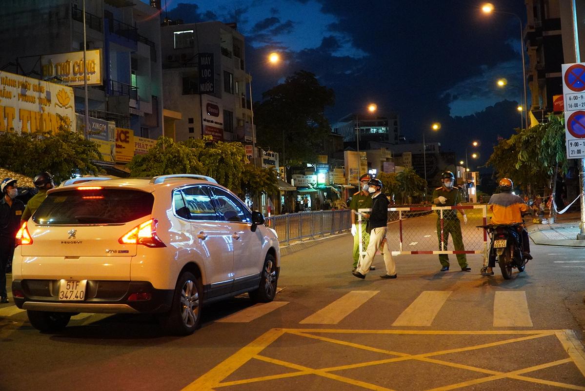 Một shipper đang giải trình với cán bộ kiểm soát tại chốt Phan Văn Trị, quận Gò Vấp, tối 26/7 về lý do về trễ sau 18h. Ảnh: Gia Minh.