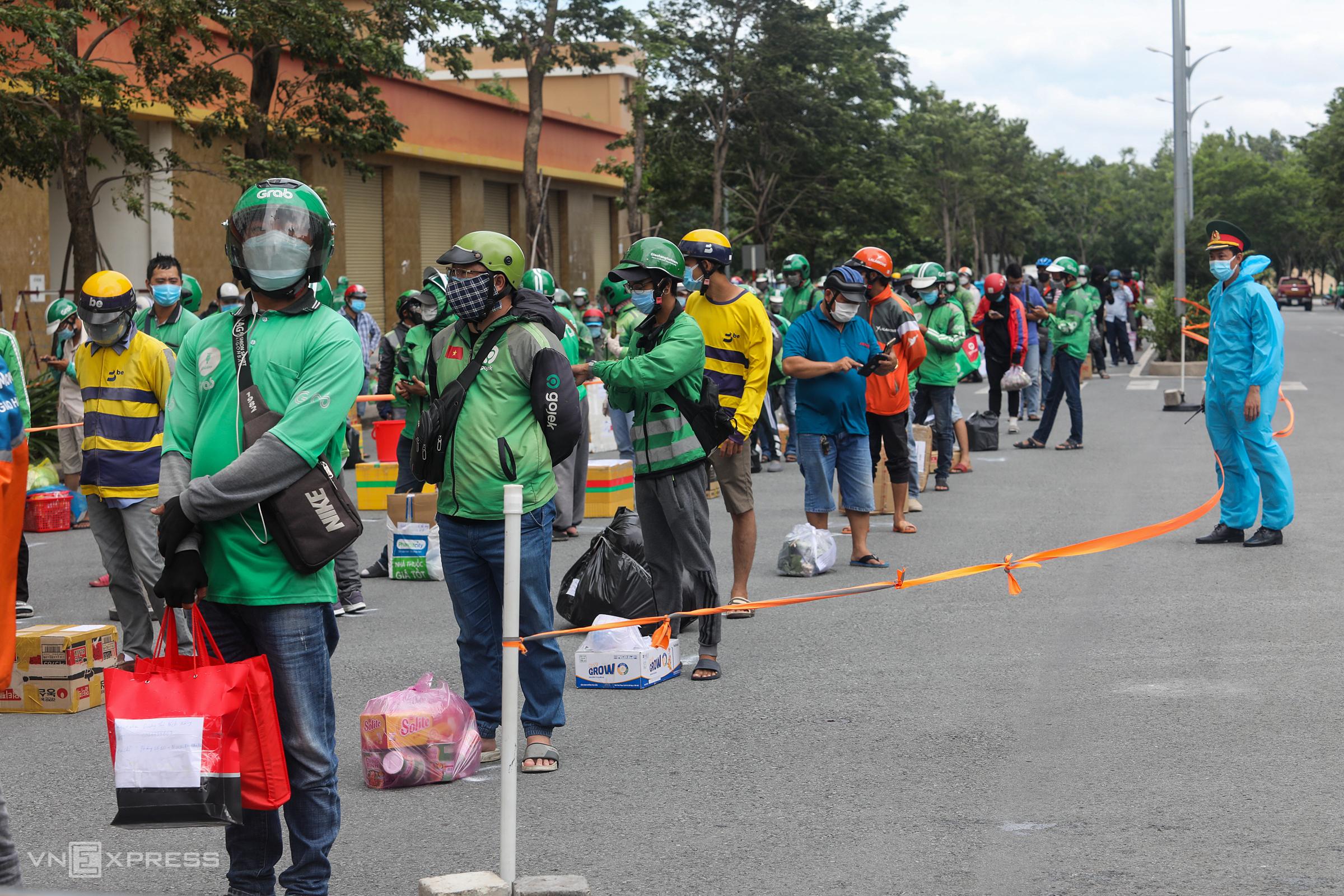 Shipper và người dân đứng xếp hàng chờ giao đồ trước Bệnh viện dã chiến số 6 (TP Thủ Đức), ngày 21/7. Ảnh: Thành Nguyễn.