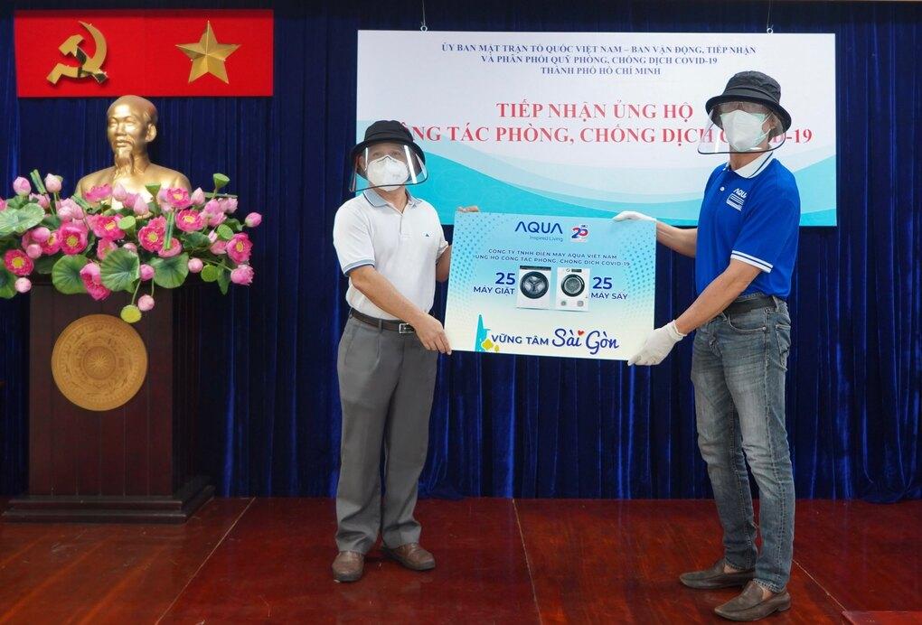 Đại diện Aqua Việt Nam (bên phải) trao tặng các sản phẩm điện máy của hãng cho đại diện Ủy ban Mặt trận Tổ Quốc Việt Nam TP HCM vào sáng 23/7.