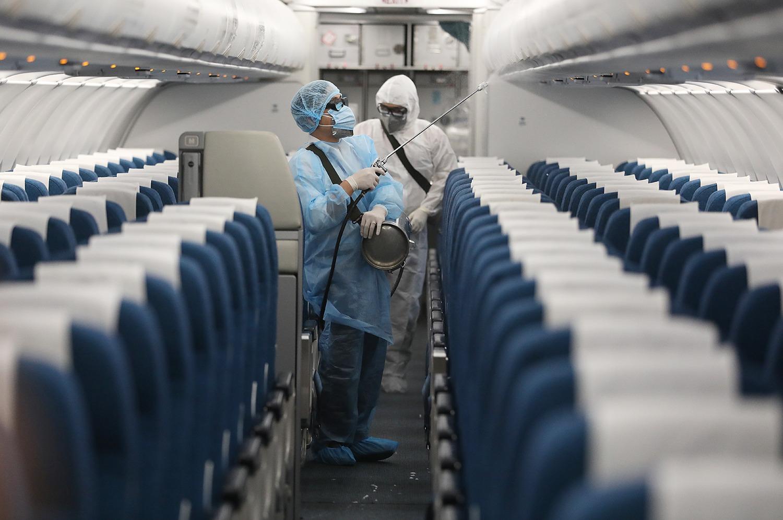 Nhân viên y tế khử trùng bên trong máy bay tại sân bay Nội Bài. Ảnh: Bá Đô