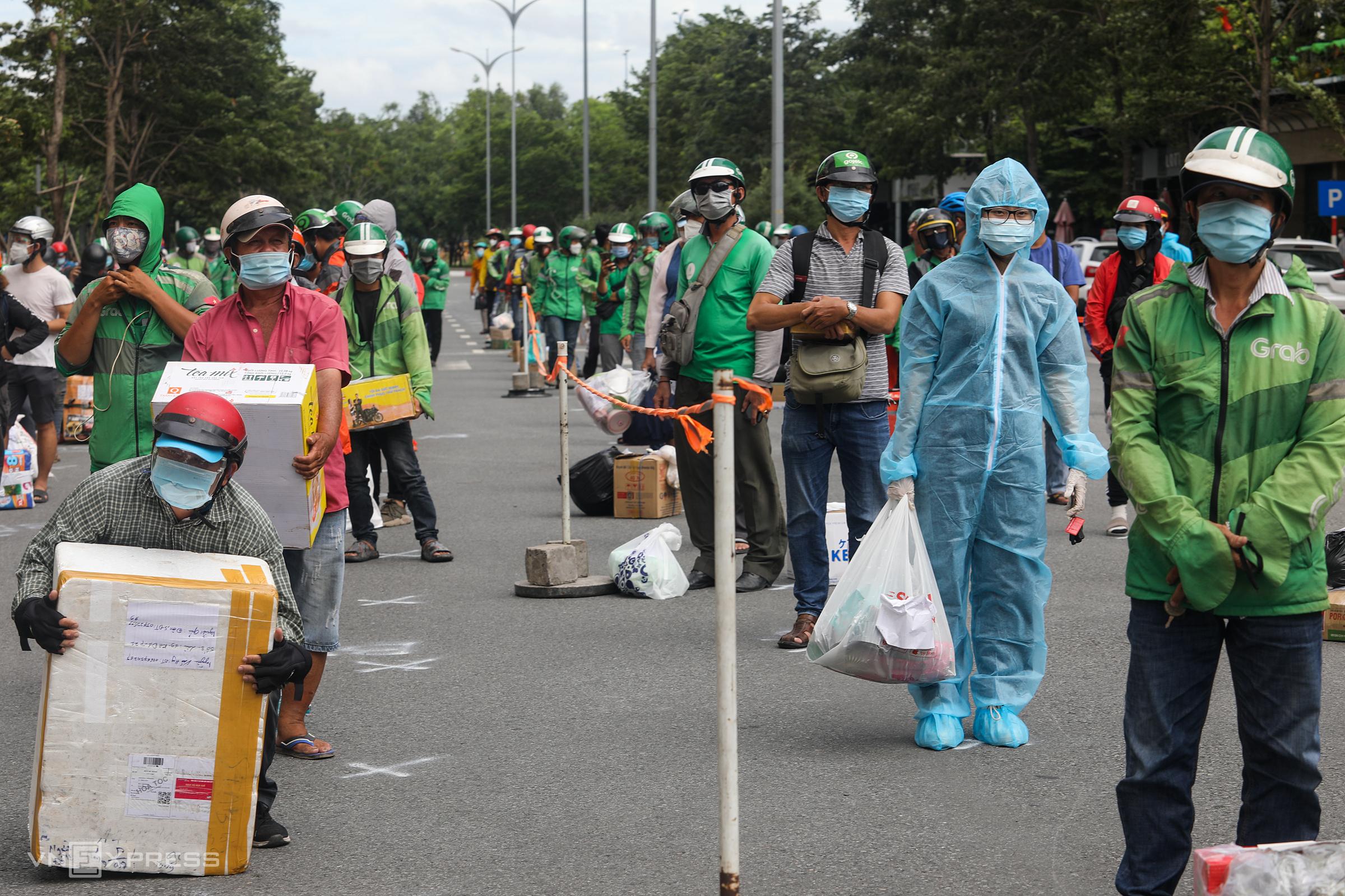 Shipper và người dân đứng xếp hàng chờ giao đồ trước Bệnh viện dã chiến số 6 (TP Thủ Đức), ngày 21/7. Ảnh: Thành Nguyễn