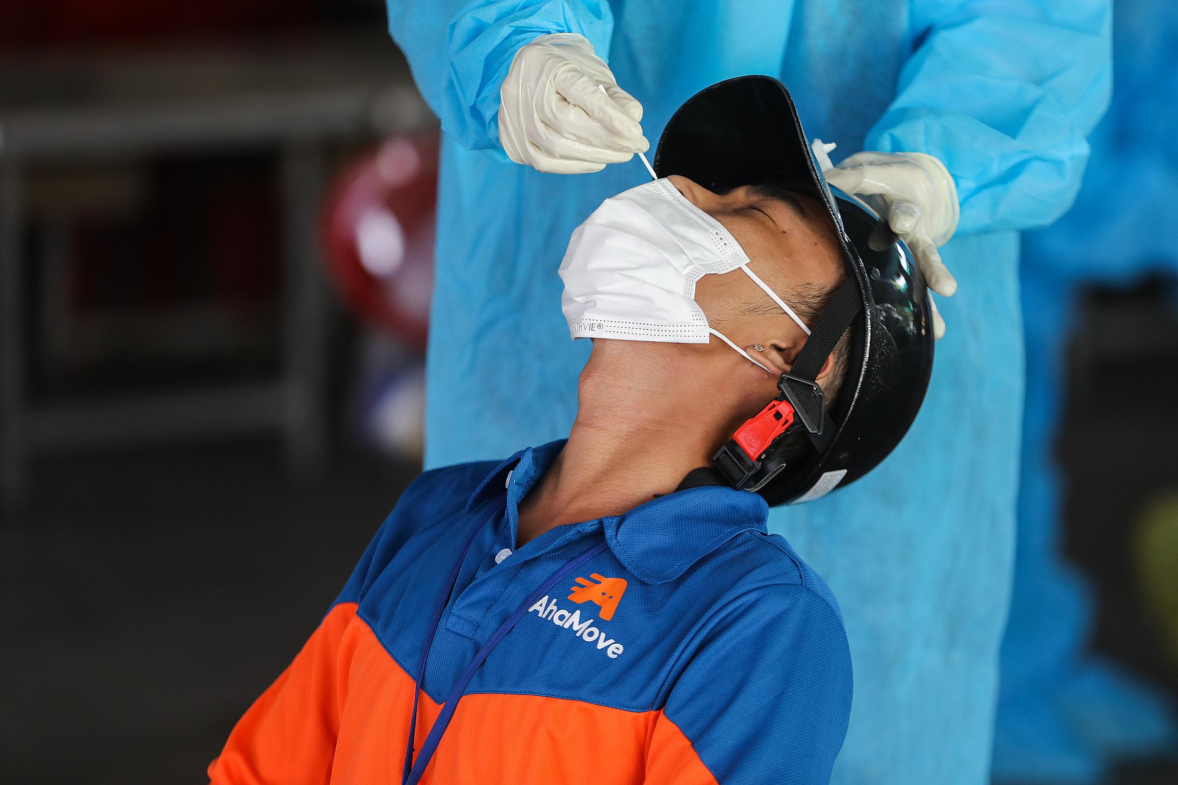 Một shipper đang được lấy mẫu xét nghiệm Covid-19 tại quận Gò Vấp. Ảnh: Quỳnh Trần